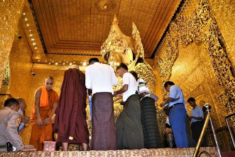 Devotos junto a buda en Myanmar